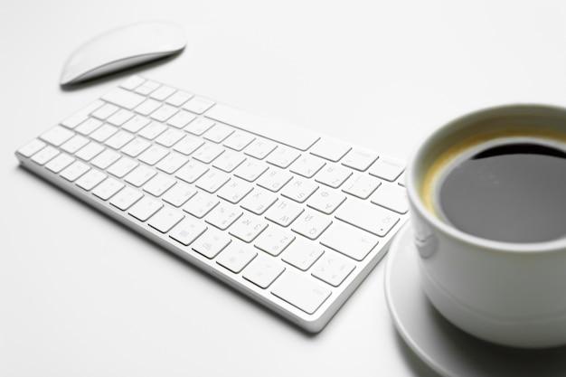 Mesa de escritório com computador, suprimentos e xícara de café