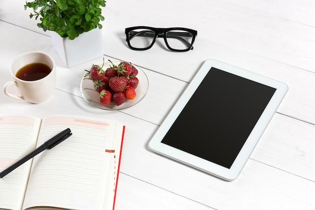 Mesa de escritório com conjunto de suprimentos, bloco de notas em branco branco, copo, caneta, tablet, óculos, flores sobre fundo branco. vista superior e copie o espaço para o texto