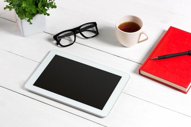 Mesa de escritório com conjunto de suprimentos bloco de notas vermelho copo caneta tablet óculos flor em fundo branco ...