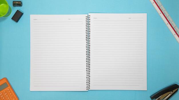 Mesa de escritório com conjunto de suprimentos coloridos, bloco de notas em branco azul, copo, caneta, pc, papel amassado, flor sobre fundo azul. vista superior e copie o espaço para o texto.
