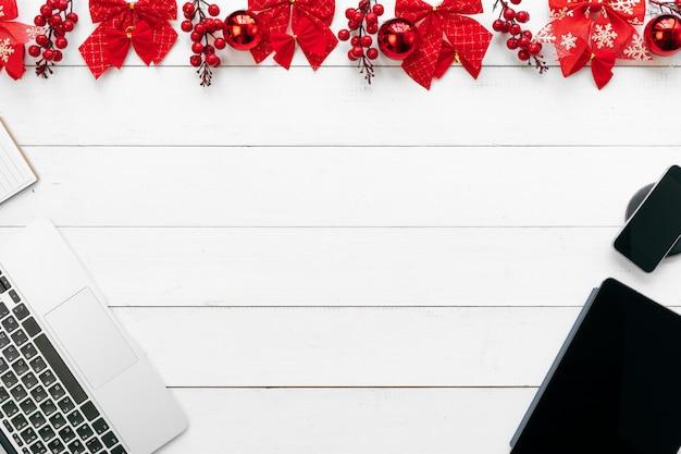 Mesa de escritório com dispositivos, suprimentos e decoração de natal. vista de cima