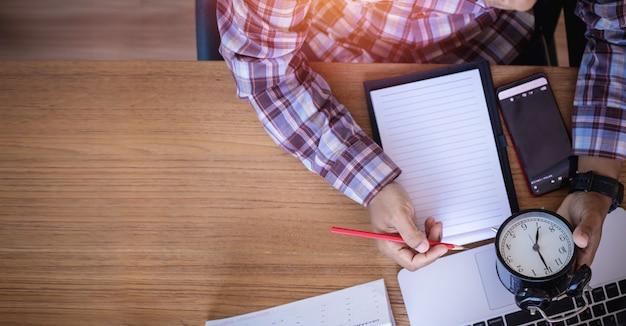 Mesa de escritório com empresário escrevendo no papel de nota e segurando o relógio clássico