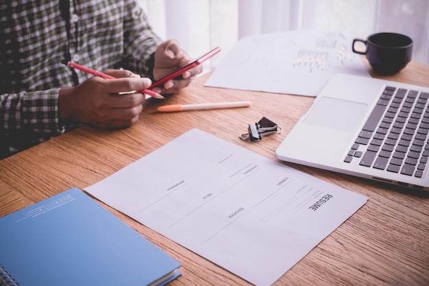Mesa de escritório com empresário preenchendo o formulário de currículo, conceito de encontrar um emprego.
