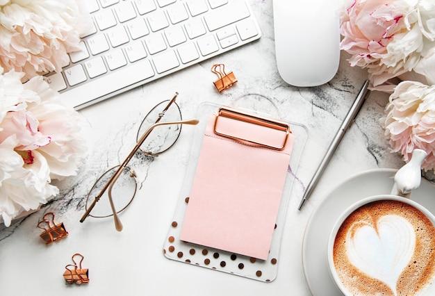 Mesa de escritório com flores de peônia rosa