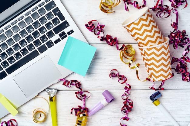 Mesa de escritório com laptop e bloco de notas aberto decorado com flâmulas de festa.