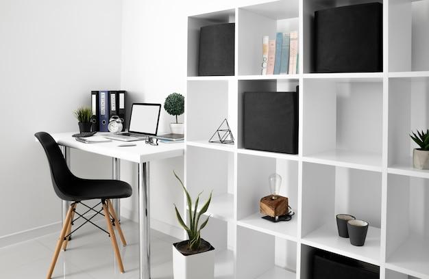 Mesa de escritório com laptop e cadeira ao lado da prateleira