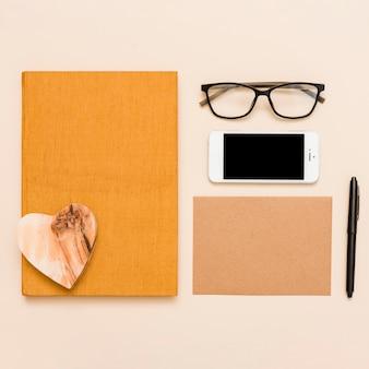 Mesa de escritório com livro, óculos e caneta