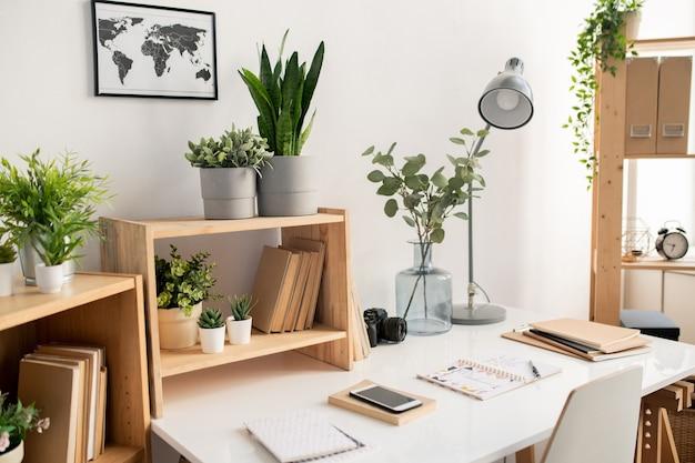 Mesa de escritório com material de trabalho e foto do mapa na parede sobre estantes de madeira com vasos de flores e livros
