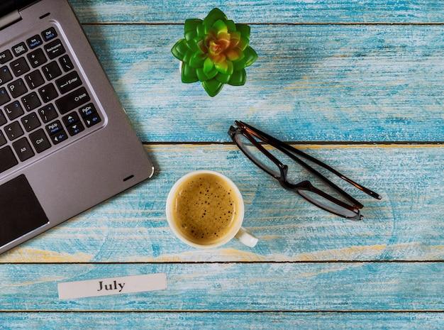 Mesa de escritório com mês de julho do ano civil, computador e xícara de café, vista de óculos