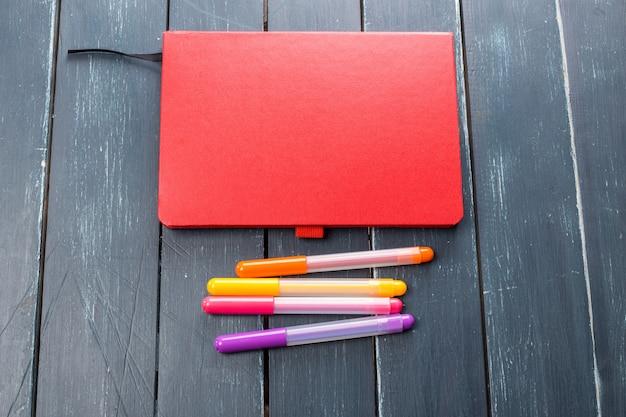 Mesa de escritório com notebook e marcadores
