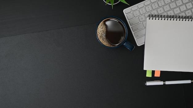 Mesa de escritório com notebook, teclado e xícara de café