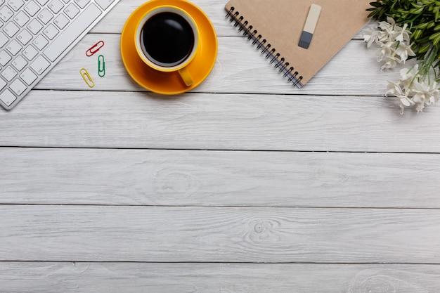 Mesa de escritório com o bloco de notas em branco e laptop