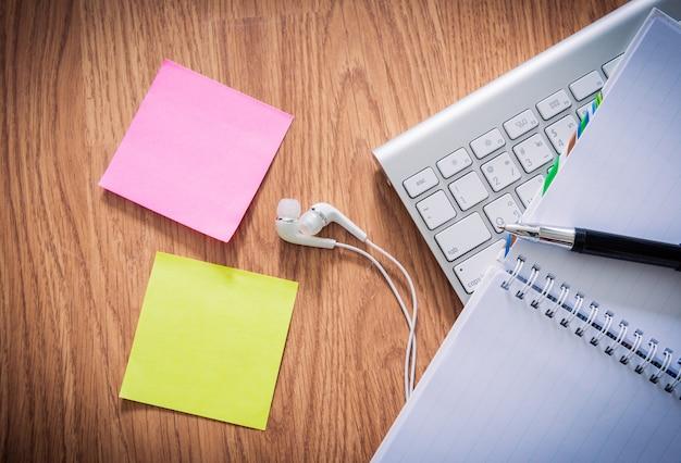 Mesa de escritório com o bloco de notas, teclado de computador, xícara de café, caneta, fone de ouvido, notas auto-adesivas