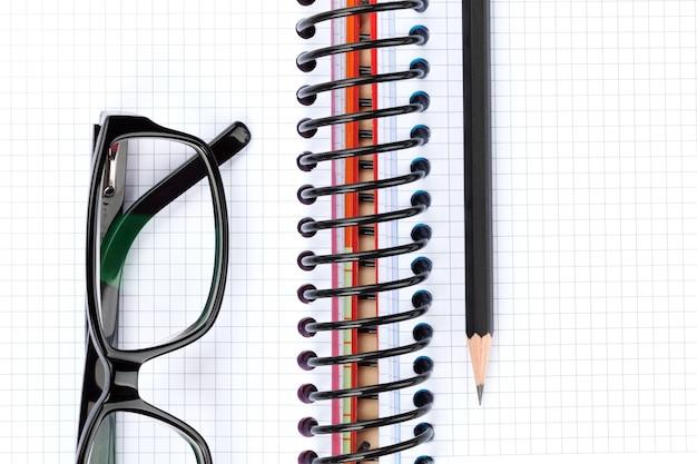 Mesa de escritório com óculos, bloco de notas em branco e lápis. vista de cima