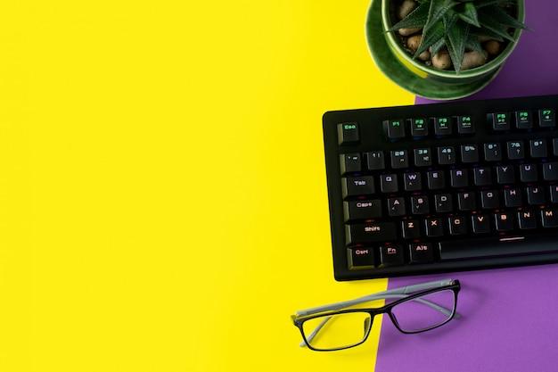 Mesa de escritório com óculos, planta e teclado. fundo com copyspace