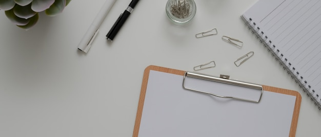 Mesa de escritório com papel na área de transferência, artigos de papelaria, agenda e outros materiais de escritório