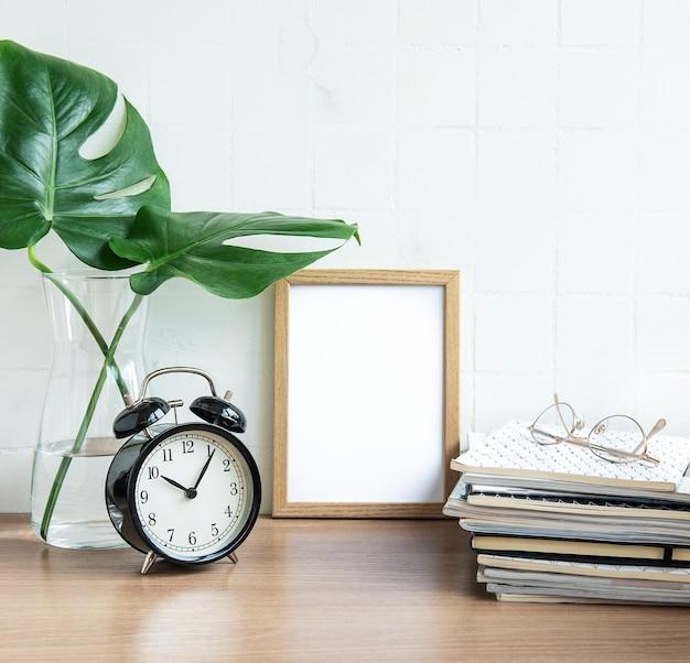 Mesa de escritório com pilha de blocos de notas, despertador, material de escritório e plantas domésticas