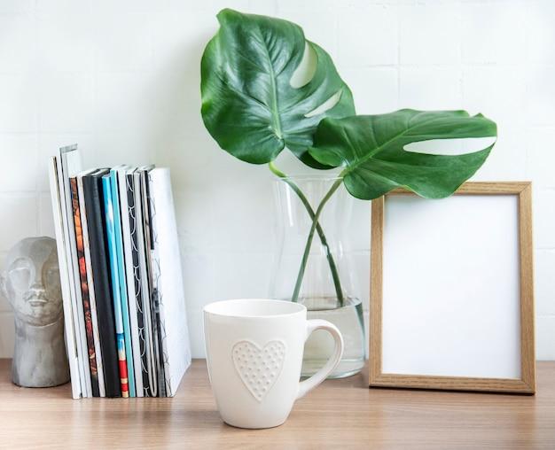 Mesa de escritório com pilha de blocos de notas, material de escritório e plantas domésticas