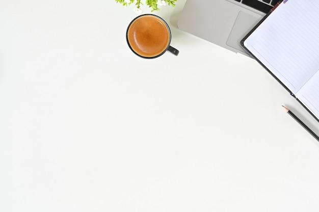 Mesa de escritório com portátil, café, caderno e lápis na opinião de tampo da mesa branca.