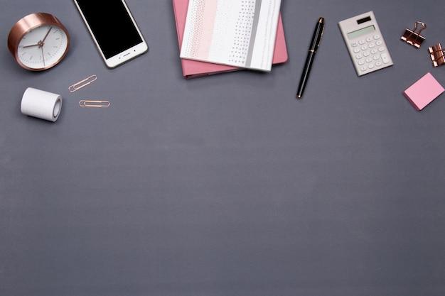 Mesa de escritório com smartphone e outros materiais de escritório em fundo cinza.