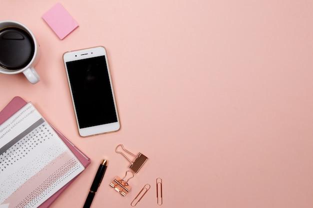 Mesa de escritório com smartphone e outros materiais de escritório em fundo rosa.