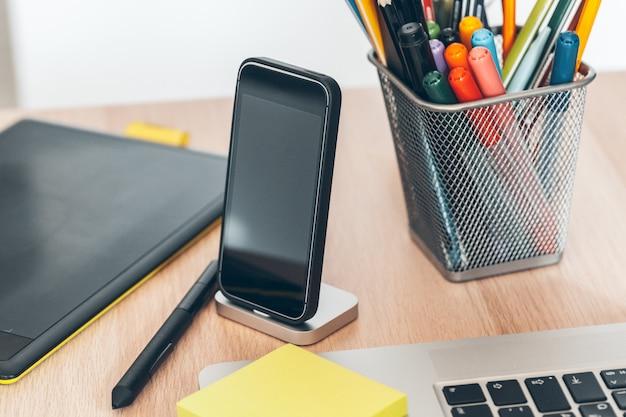 Mesa de escritório com smartphone e suprimentos close-up, interior do escritório