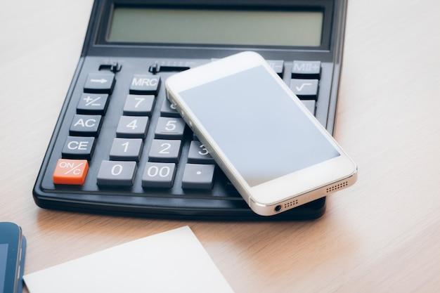 Mesa de escritório com smartphone e suprimentos close-up