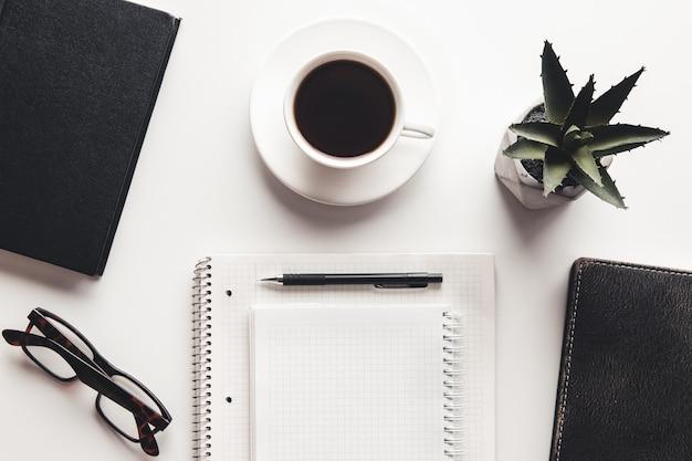 Mesa de escritório com suprimentos, xícara de café e flores