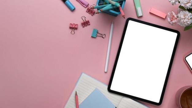 Mesa de escritório com tablet digital, bouquet e artigos de papelaria em fundo rosa.