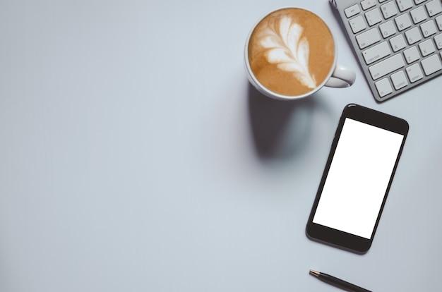 Mesa de escritório com teclado, computador, caneta, café e telefone inteligente em fundo cinza tom vintage