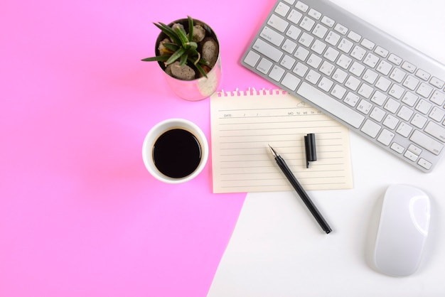 Mesa de escritório com teclado, mouse, notebook e smartphone em dois tons (branco e rosa) ba