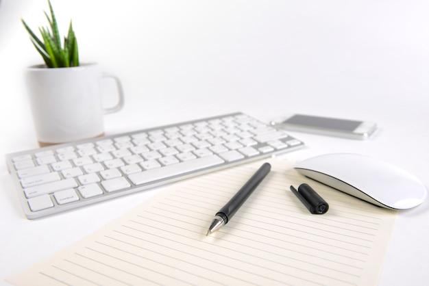 Mesa de escritório com teclado, mouse, notebook e smartphone em fundo branco.