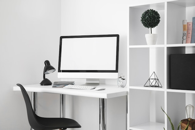 Mesa de escritório com tela de computador e cadeira