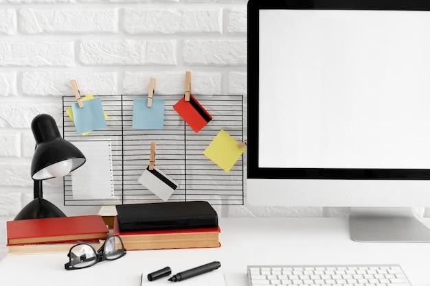 Mesa de escritório com tela de computador e lâmpada