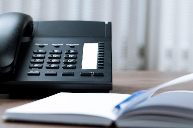 Mesa de escritório com telefone e agenda