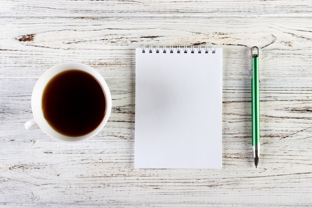 Mesa de escritório com uma xícara de café e o bloco de notas