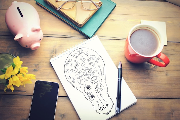 Mesa de escritório com uma xícara de café, plano no bloco de notas