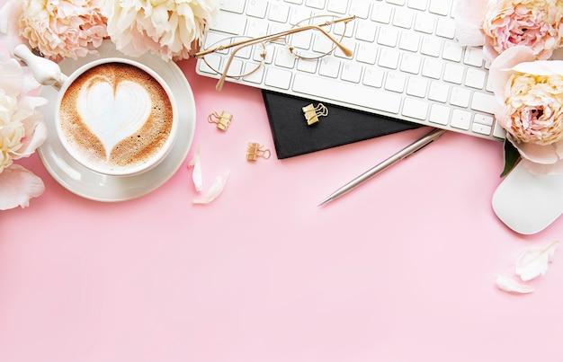 Mesa de escritório com xícara de café e flores de peônia