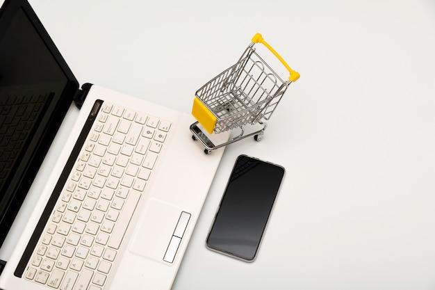 Mesa de escritório, computador com telefone inteligente e carrinho de compras isolado
