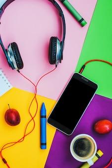 Mesa de escritório de acessórios de vista superior. fones de ouvido de smartphones em fundo colorido