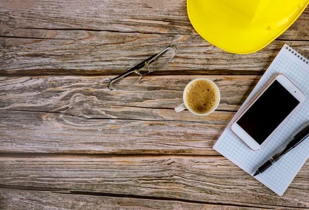 Mesa de escritório de arquiteto de construtores de espaço de trabalho, caderno aberto em branco com caneta no capacete amarelo com uma xícara de café, óculos de smartphone na mesa de madeira