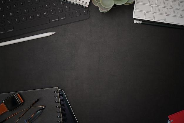 Mesa de escritório de couro escuro com gadget de escritório em casa e espaço de cópia
