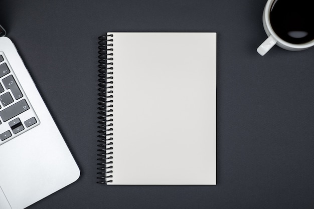 Mesa de escritório de design com página de caderno em branco e computador portátil