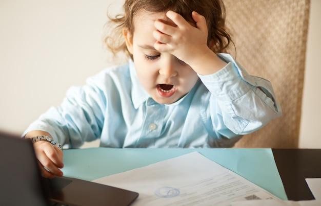 Mesa de escritório de espaço de trabalho com o laptop. menina bonitinha negócios sentado à mesa e olhando para um documentos importantes. garoto aprendendo online.