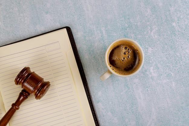 Mesa de escritório de justiça judiciária com suprimentos, xícara de café em um martelo de juiz