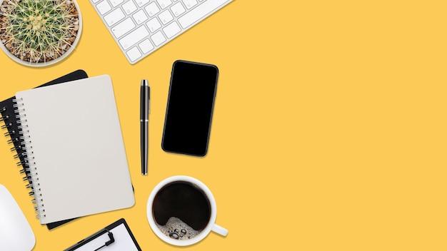 Mesa de escritório de madeira amarela de vista superior com computador e material de escritório