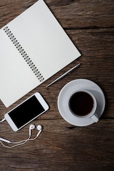 Mesa de escritório de madeira com caneta, bloco de notas, xícara de café, smartphone e fones de ouvido. vista do topo