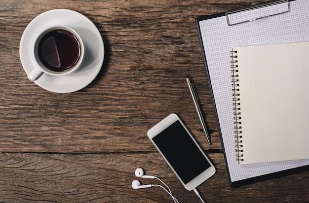 Mesa de escritório de madeira com caneta, bloco de notas, xícara de café, smartphone e fones de ouvido