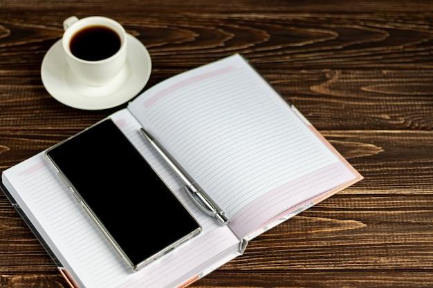 Mesa de escritório de madeira com muitas coisas. diário com caneta, telefone samsung. branca xícara de café.