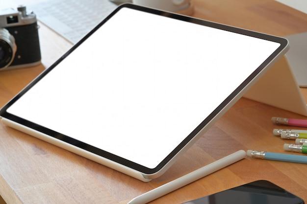 Mesa de escritório de madeira de área de trabalho com tablet de tela em branco de maquete